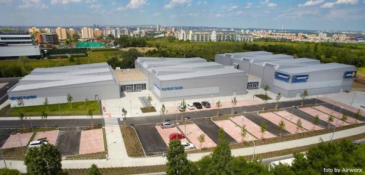 Pohled na parkoviště a tři haly volnočasového sportovního centra Jedenáctka Chodov.